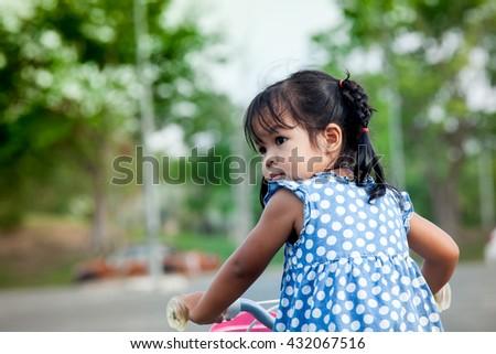 Child cute little girl riding bike in park - stock photo