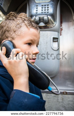 Child dials a phone number in a phone booth