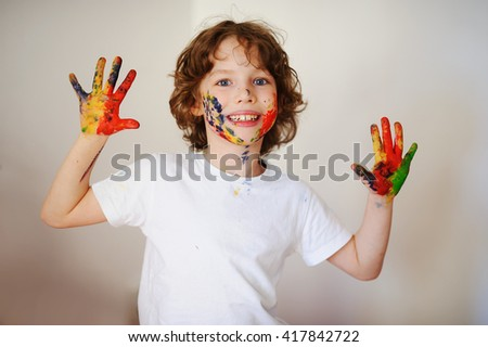 Child dirty of paint looking at the camera. Child has fun painting / drawing. Children's creativity. Art for baby. Emotions - stock photo