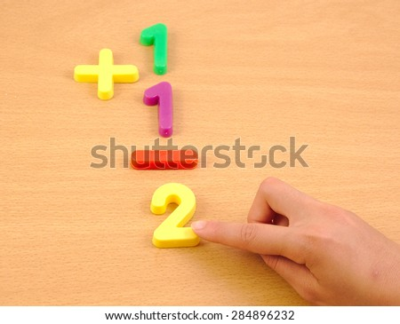Child doing a sum with plastic items on the school wood desk - stock photo