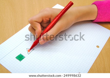 Child drawing a red triangle and a green square with a red wax crayon - stock photo