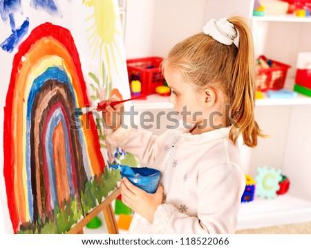 Child drawing on the easel at school. - stock photo