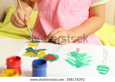 Child drawing with bright paints on paper, closeup - stock photo