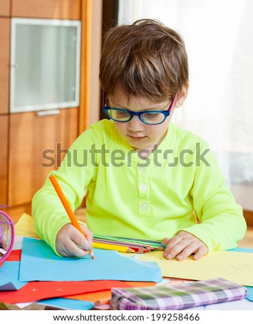 Child drawing with crayons at  table.