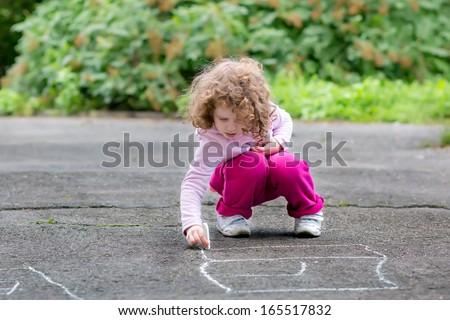 Child draws on asphalt - stock photo