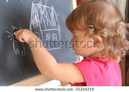 child draws with chalk on the blackboard - stock photo