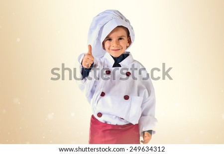 child dressed as a chef with thumb up - stock photo