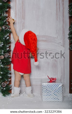 Child dressed as Santa with gift opens door for Christmas - stock photo