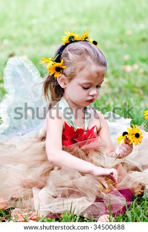 Child dressed up in a costume as a woodland fairy for Halloween gathering flowers.