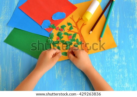 Child drew a brown tree trunk. Child tears colored paper into small pieces. Torn paper edge. Torn paper art project for kids. Creativity lesson in kindergarten. Pencils, glue stick. - stock photo