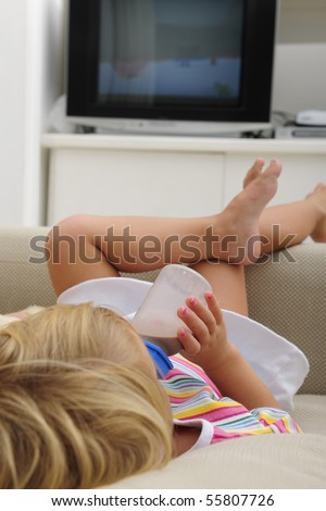 Child drinking chocolate milk in a bottle, lying alone on the couch and watching TV in DVD file