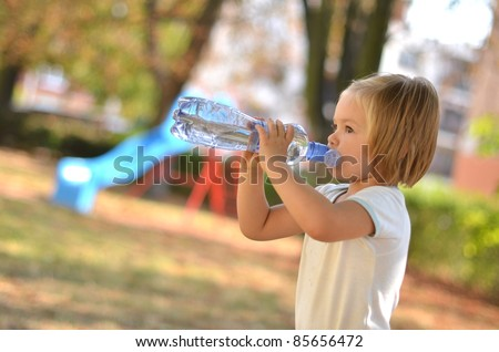 Child drinking pure water in nature - stock photo