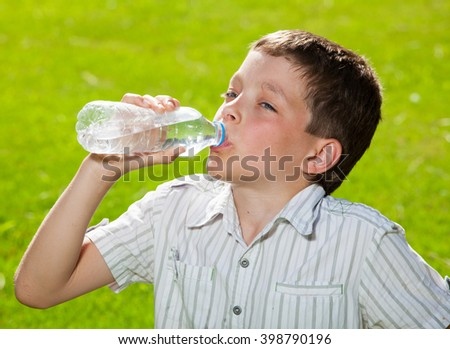 Child drinking water. Boy outdoors