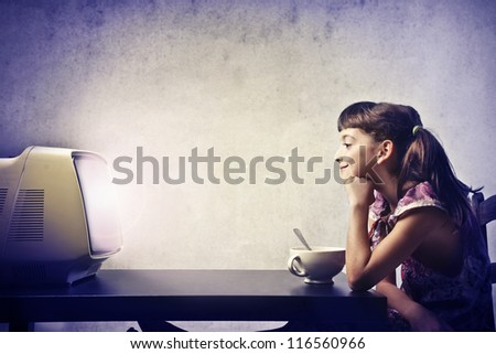 Child, during the breakfast, watching the TV - stock photo