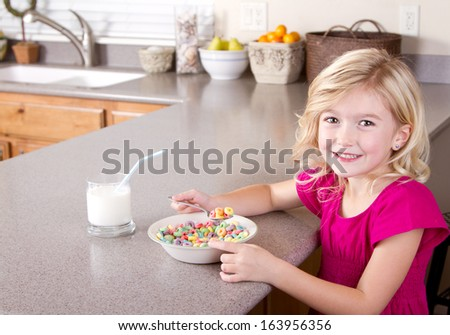 Child eating a bowl of cereal with glass of milk in kitchen at home
