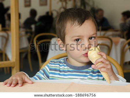 Child eating a cone ice cream at a table at a cafe.  - stock photo