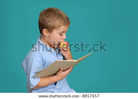 Child eating an apple and reading a book - stock photo