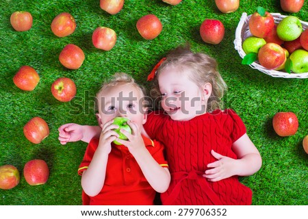 Child eating apple. Little girl and baby boy play peek a boo holding fresh ripe apples. Kids eat snack relaxing on a lawn. Children summer fun on a farm picking healthy fruit. - stock photo
