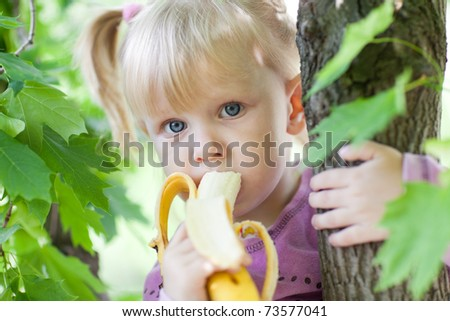child eating banana on the tree - stock photo