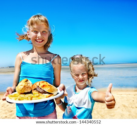 Child eating fast food at beach outdoor. - stock photo