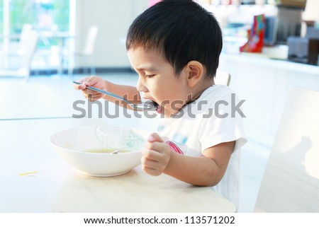 Child eating food in home. - stock photo