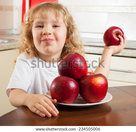 Child eating fruits. Girl at kitchen with apple - stock photo