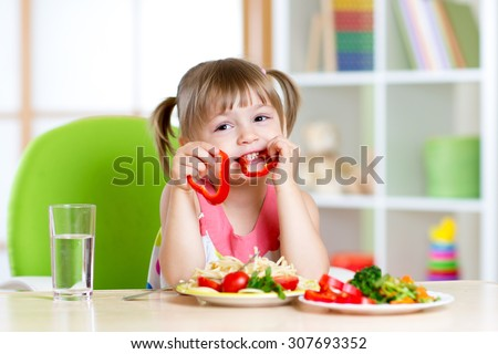 child eating healthy food in kindergarten or at home - stock photo