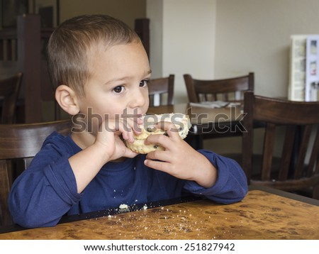 Child eating rock cake in a cafe. - stock photo