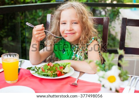 Child eating salad at a cafe. Girl eating outdoors - stock photo