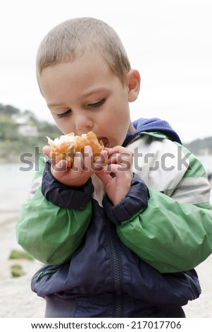 Child eating takeaway meal of fish and chips outdoor at english seaside.