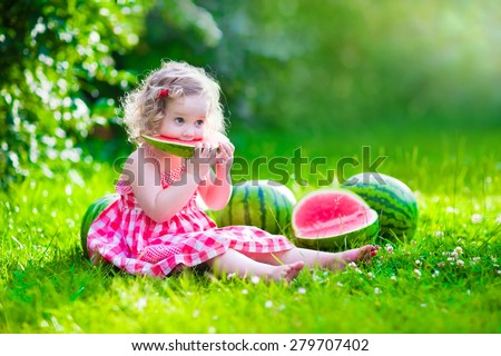 Child eating watermelon in the garden. Kids eat fruit outdoors. Healthy snack for children. Little girl playing in the garden holding a slice of water melon. Kid gardening. - stock photo