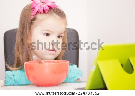 child eats and looks at tablet computer - stock photo