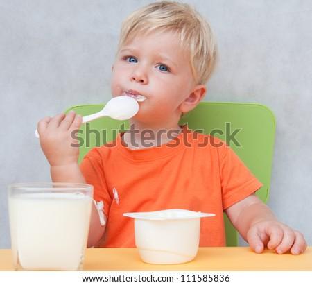 Child eats yogurt - stock photo