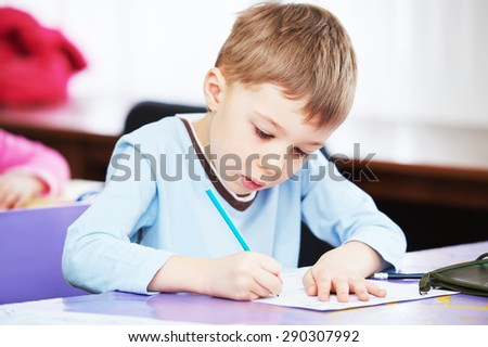 Child education. boy studying writing at the classroom