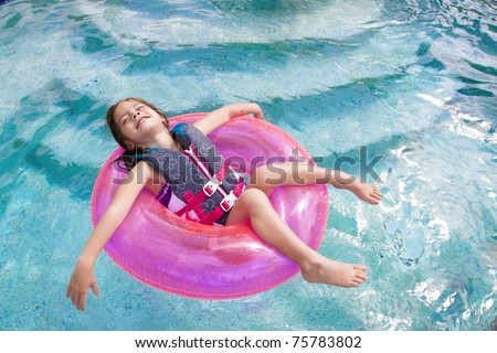 Child enjoying playing in the swimming pool - stock photo