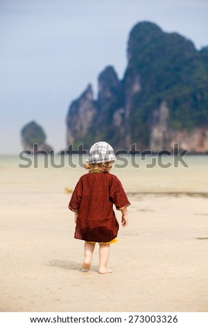 Child enjoying the low tides, walking on fine sand on a tropical beach. Fearless, intrepid and adventurous childhood concept.