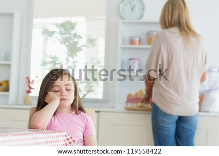 Child falling asleep at kitchen table with mother working on counter - stock photo