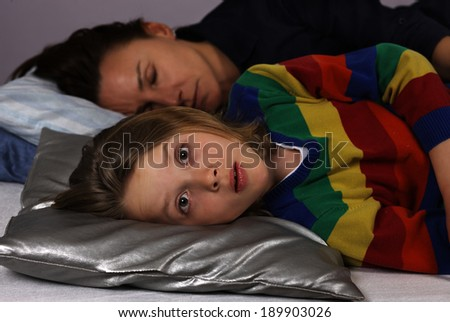 Child fear at night lying awake, with sleeping mother in background - stock photo