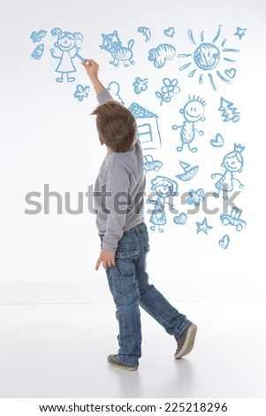 child fills wall with some symbols and objects - stock photo