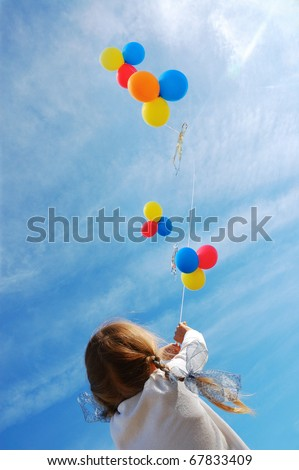 Many Beautiful Balloons In The Sky : child flying colorful balloons in the blue sky - stock photo