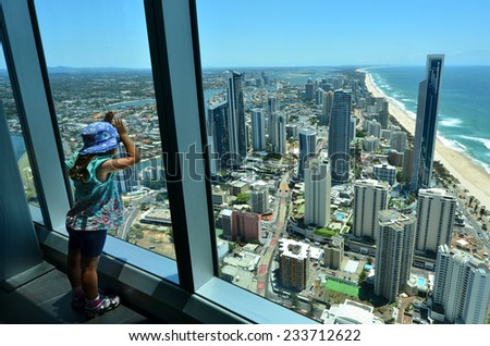 Child (girl age 04) looks at the view of Surfers Paradise from the Skypoint observation deck at the top of the Q1 on the Gold Coast, Australia. - stock photo