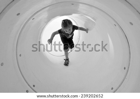 Child (girl age 05) plays in playground tunnel. Concept photo childhood. copy space (BW) - stock photo