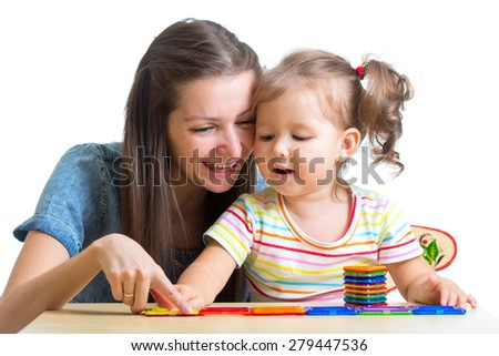 child girl and mom playing together with toys isolated - stock photo