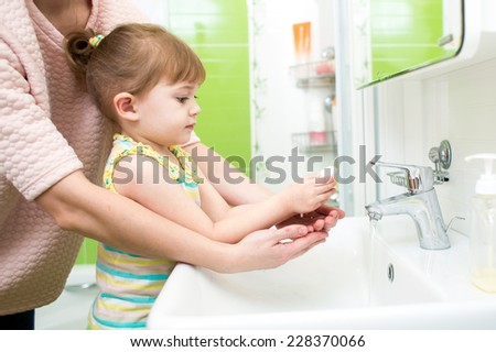child girl  and mother washing hands with soap in bathroom - stock photo