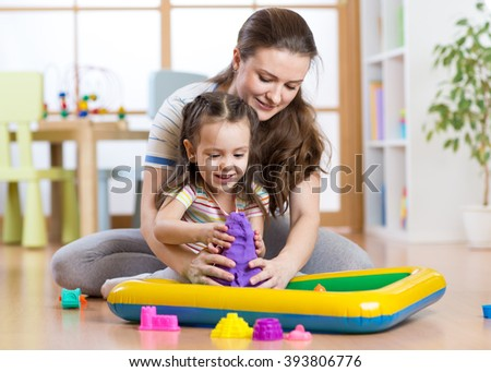 Child girl and woman mould with kinetic sand in playschool or daycare - stock photo