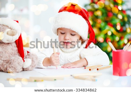 child girl before Christmas writes a letter to Santa Claus - stock photo