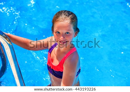 Child girl coming out of swimming pool . Pool steps on foreground. Summer holiday. Outdoor. - stock photo