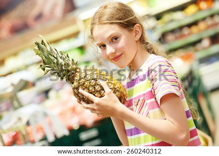 child girl during shopping with pineapple fruit at supermarket - stock photo