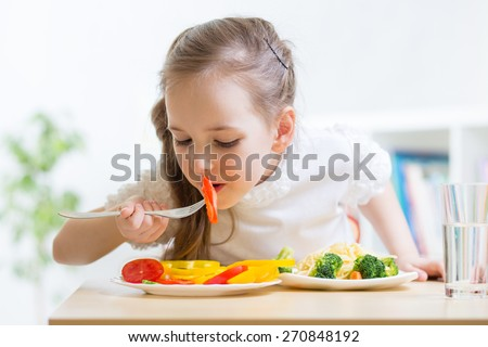 child girl eating healthy food at home - stock photo