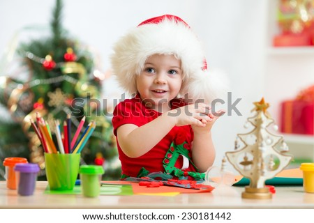 child girl in Santa hat making christmas tree of plasticine - stock photo
